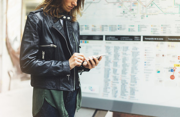 Fotomurales - Girl in leather jacket holding smart phone on background map light box in sun city, hipster using in female hands and texting mobile, glitter street lifestyle, tourist planing route in summer concept