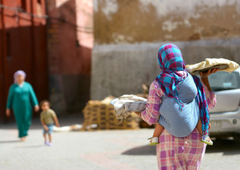 Moroccan woman with a child behind her, sells bread on the streets of the city