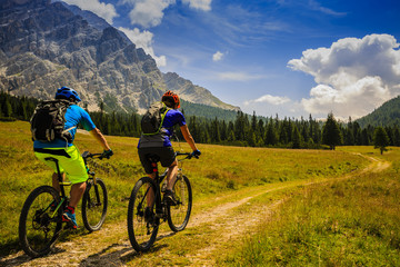 Photo sur Toile Cyclisme Mountain cycling couple with bikes on track, Cortina d'Ampezzo, Dolomites, Italy