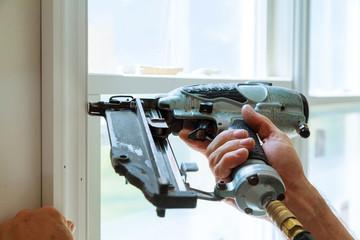 Carpenter brad using nail gun to moldings on windows, framing trim,