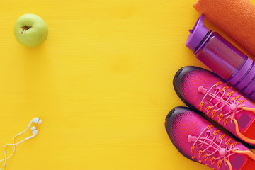 fitness concept with bottle of water, towel and woman pink sport footwear over colorful background