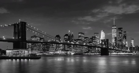 Fotomurales - Time-lapse of Lower Manhattan Financial District skyscrapers, Brooklyn Bridge, and East River with passing clouds at twilight in Black & White. Manhattan, New York City