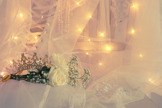Beautiful white wedding dress, tiara and veil on chair with gold garland lights