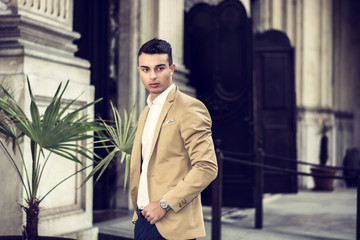 Elegant attractive young man outdoor wearing business suit, in European city