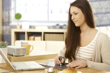 Young woman using drawing pad