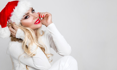 Beautiful sexy blonde female model dressed as Santa Claus in a red cap with at the White fur lovely makeup sensual lips, christmas