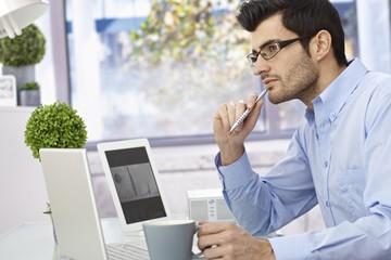 Young man thinking at desk