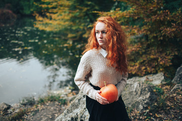 redhead girl holding pumpkin in autumn park