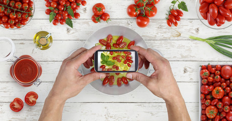 hands taking photo of food with the smartphone from above saucepan and tomatoes sauce on kitchen white wooden worktop, copy space, top view