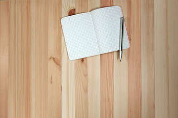 Blank paper notebook on wooden desk with top view for background or backdrop