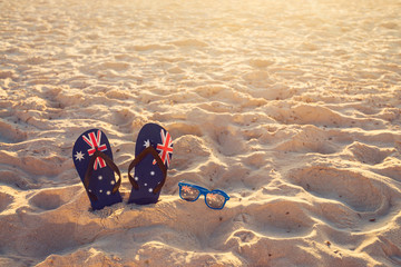 Thongs and sunglasses on beach sand