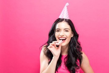 Young woman with party theme on a pink background