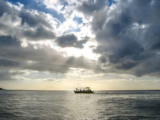 Fishing boat in the Caribbean sea at sunset with low clouds in the sky over the sea.