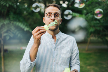 Young man in glasses playing with bubble wands in park