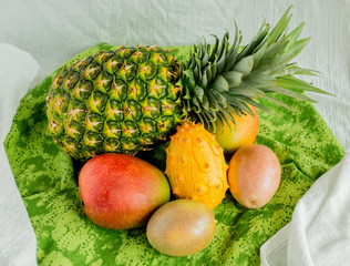 pineapple, mangoes, passion fruit and kiwano melon on a green cloth