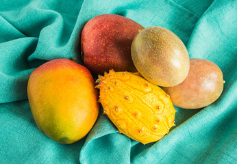 mangoes, passion fruit and kiwano melon on a green cloth