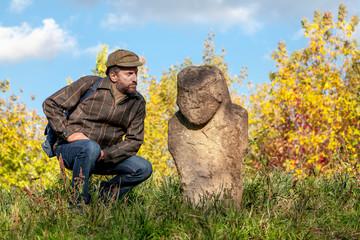 Scientist examines beard stone sculpture on mound