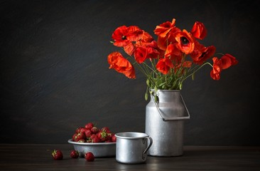 Still life in a rustic style: aluminum plate and can, bouquet of red poppies and strawberry on a wooden table.