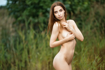 Outdoors portrait of a beautiful woman with perfect slim body posing naked.