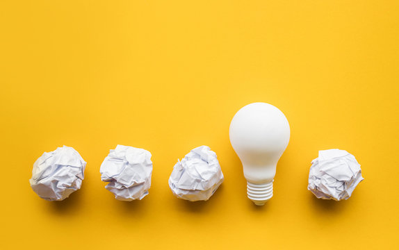 Creativity inspiration,ideas concept with lightbulb and paper crumpled ball on pastel color background.Flat lay design.