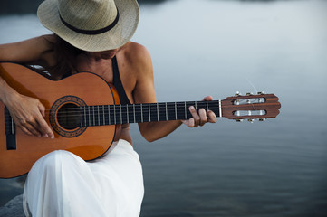 Woman with hat in the lake With guitar