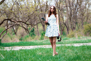 Woman or girl in a dress, with laptop and headphones happy in the park