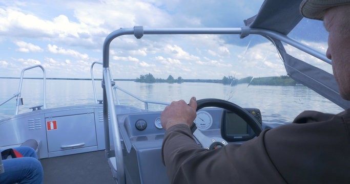 Old man driving a fast boat on the lake