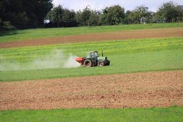 Traktor bringt Dünger auf dem Feld aus