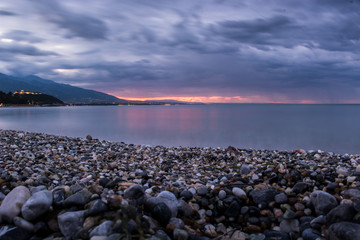 Night seascape, amazing view of pebble coastline in mild sunset light