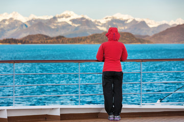 Wall Mural - Alaska cruise travel tourist woman watching nature landscape from boat standing in cold morning weather with winter jacket in inside passage, Glacier Bay, USA.