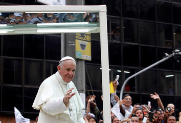 Pope Francis waves to the crowd from the popemobile after visiting an orphanage in Medellin, Colombia in his way to La Macarena stadium