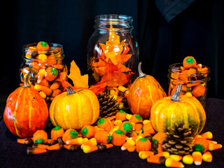 Delicious candy corn in glass jars with pumpkin squash, maple leaves make up a Halloween display.