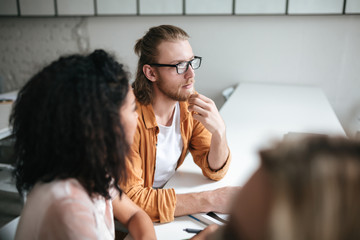 Portrait of young man with blond hair and beard dreamily looking aside while sitting with friends. Thoughtful boy in glasses sitting in office and working with friends