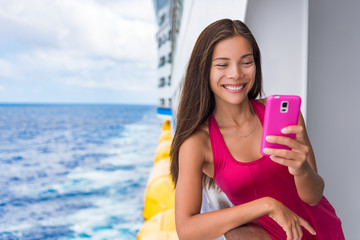 Cruise ship woman using mobile phone on travel vacation at ocean. Asian girl texting sms on boat wifi cellular data cellphone service on tropical holidays. Internet on international seas concept.