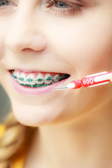 Woman with teeth braces using interdental brush