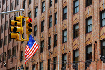 Four American Flags Waving On Flagpoles Protruding From Side of Building in NewYork City