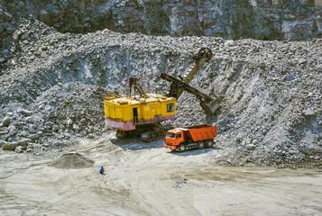 huge excavator, truck and man standing next on granite quarry