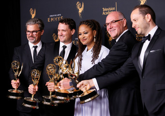 """Producer Ava DuVernay poses with her two Emmy Awards for Outstanding Documentary or Nonfiction Special and Outstanding Writing for a Nonfiction she won for """"13th"""" along with others backstage at the 2017 Creative Arts Emmy Awards in Los Angeles"""