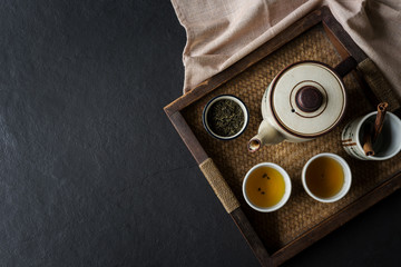 Tea set on wooden tray on black stone background