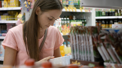 Portrait of woman choosing goods at grocery department of shopping mall