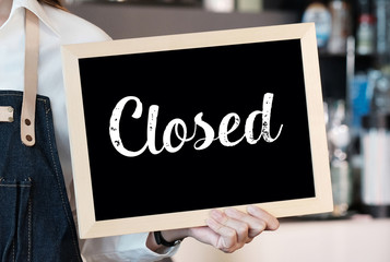 Hand holding closed sign chalkboard in font of cafe counter background, food and drinks