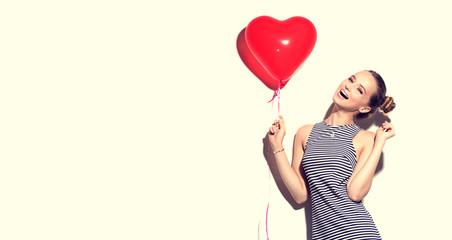 Beauty joyful teenage girl with red heart shaped air balloon