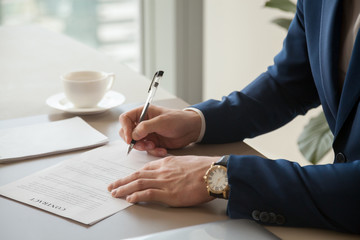 Businessman in blue business suit and expensive watch on hand putting signature on contract lying on desk. Successful investor agreeing to finance perspective project, buying company assets. Close up