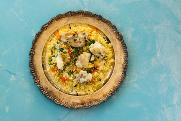 Couscous with fish and vegetables on stone table