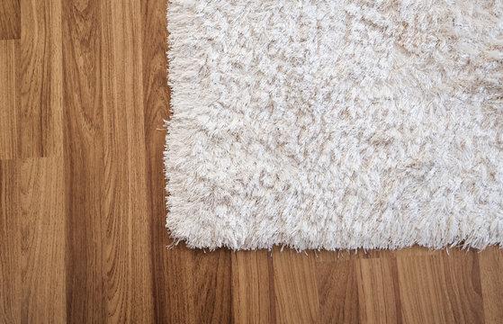 Close-up white carpet on laminate wood floor in living room, interior decoration