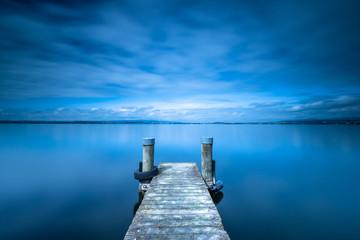 Overcast. Wooden pier. Lake to the horizon. Long exposure.