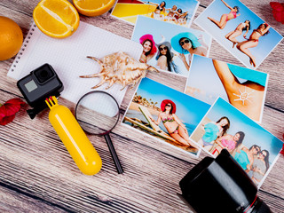 Many photos of girls in a swimsuit and a camera and goupro on a wooden table. Photo album of young women at the resort