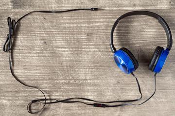 Blue headphones on wooden background