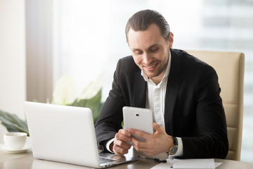 Smart young smiling handsome businessman in modern office in front of laptop looking at electronic tablet. Receiving good news, startup and entrepreneurship, financial success and investing concept.