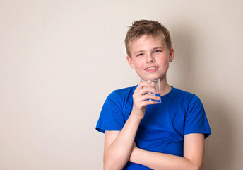 Boy with glass of water isolated with copyspace. Smiling teenager drinking water.